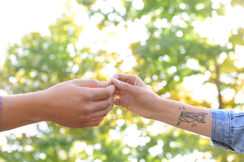 Man and woman touching fingers outdoors stock photography