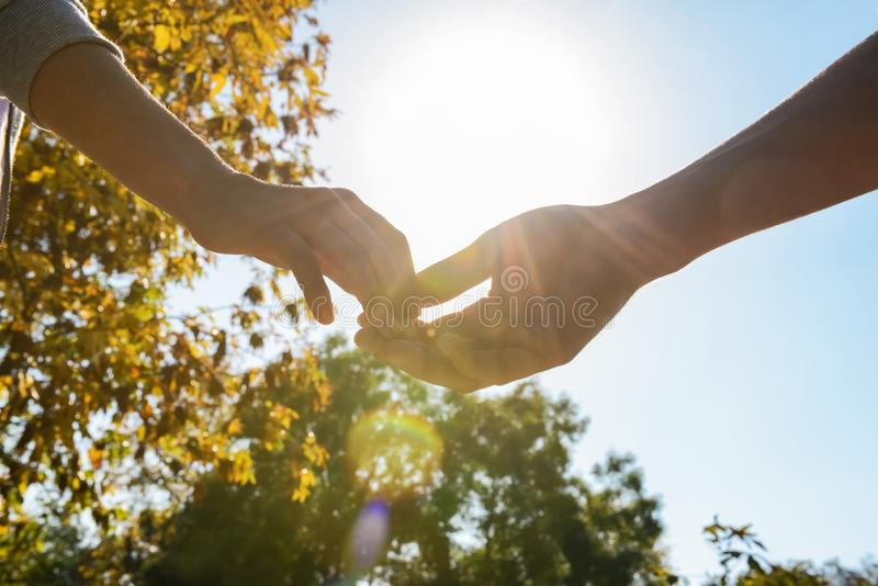 Man and woman touching fingers outdoors stock photo