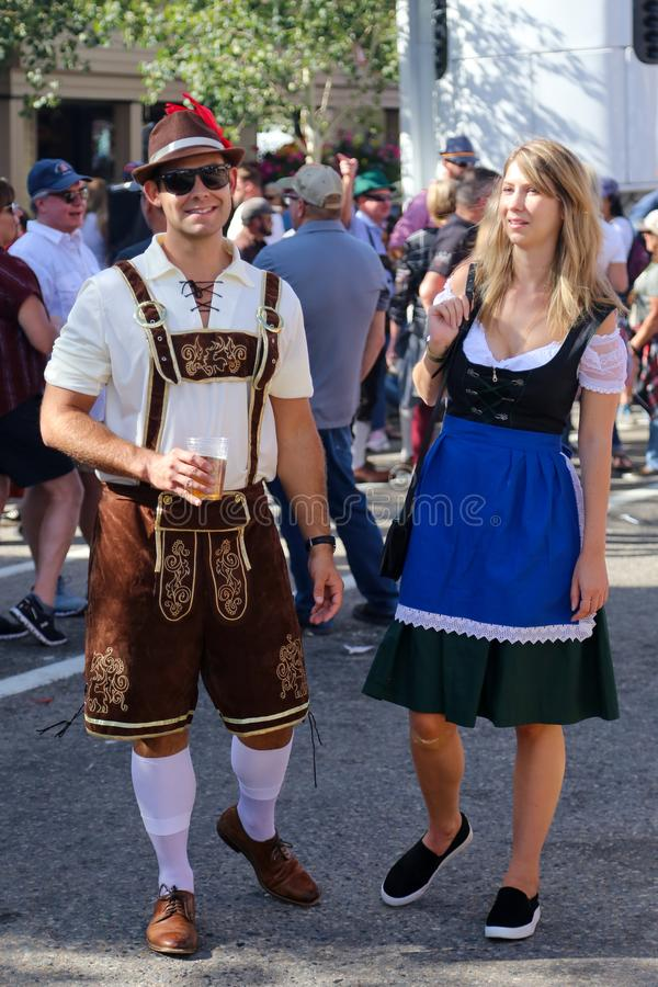 Bavarian couple drinking in the street during Oktoberfest royalty free stock photos