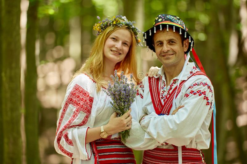 Man and woman in traditional costumes. Romanian couple in traditional costumes in the forest stock photos