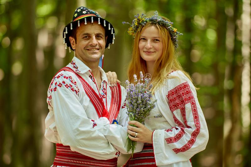 Man and woman in traditional costumes. Romanian couple in traditional costumes in the forest stock photography