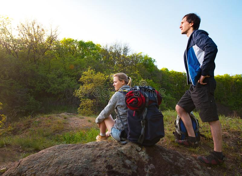 Man and woman traveler outdoors.Couple of Hikers with backpacks stock images