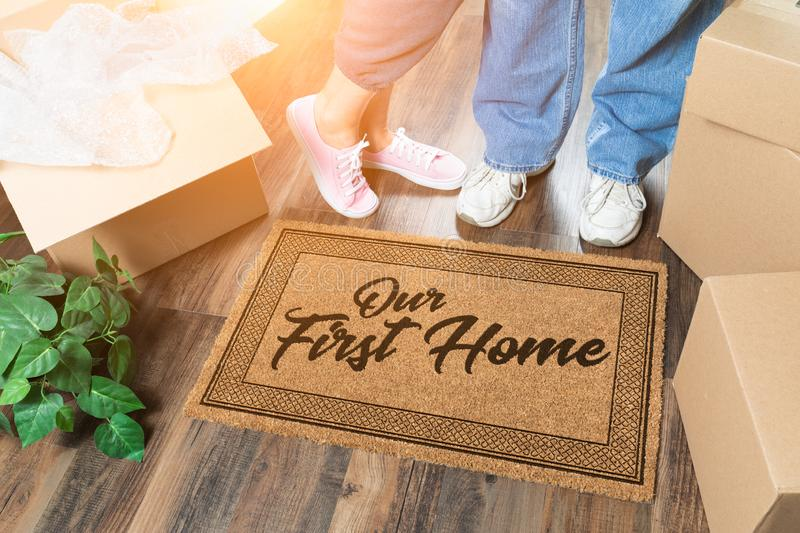 Man and Woman Unpacking Near Our First Home Welcome Mat, Moving Boxes and Plant. Man and Woman Unpacking Near Our First Home Welcome Mat, Moving Boxes and a royalty free stock photo