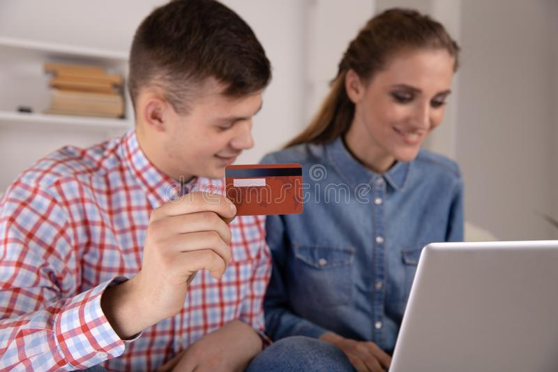 Man and woman using internet sitting at home and making shopping online. stock photos