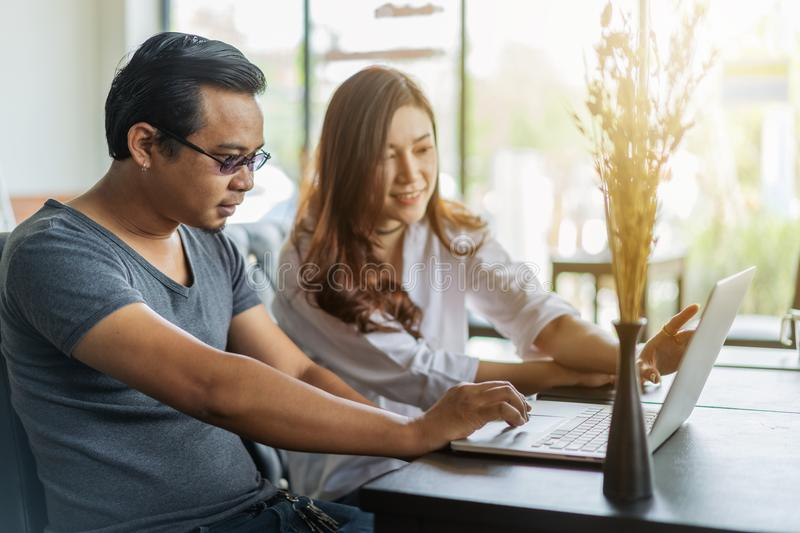 Man and woman using laptop in cafe royalty free stock images