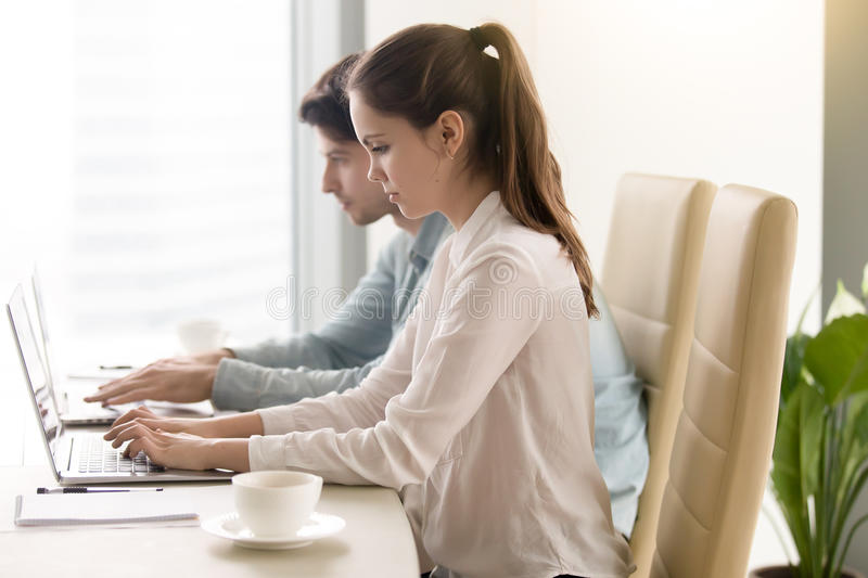 Man and woman using laptops, coworking. Working at office, meeti stock images