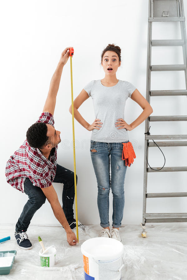 Man and woman using measure tape. Man using measure tape to measure his shocked glad wowan standing near ladder stock photography