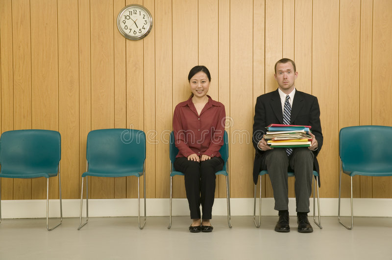 Man and Woman in Waiting Room. A amiling woman and surprised looking man sitting in a waitng room together stock photo