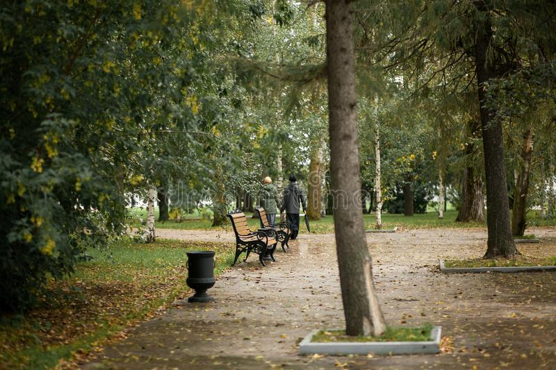 A man and a woman walk in the Park along the path on a cloudy autumn day. Minister of the Church with his wife, holding hands on a royalty free stock image