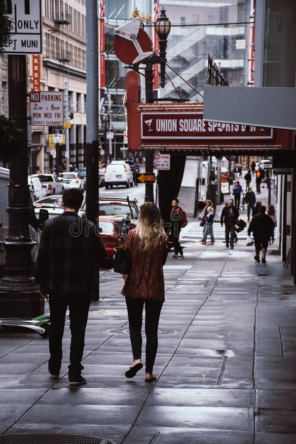 Man and Woman Walk Beside Store royalty free stock photo