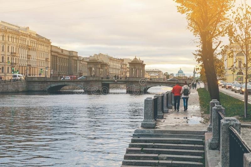 A man and a woman are walking along the embankment of a river stock photo