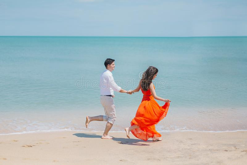 Man and Woman Walks Beside Green Sea stock photos