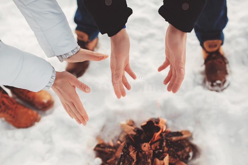 Man and woman warm their hands near fire. The concept of lover at winter camping, hiking, recreation, tourism or destitute, homeless,, disadvantaged, lost astray stock images