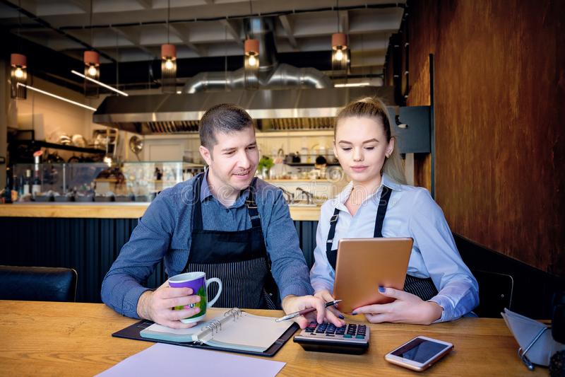Man and woman wearing apron doing accounts after hours in a small restaurant. Employees checking monthly reports. Man and women wearing apron doing accounts royalty free stock images