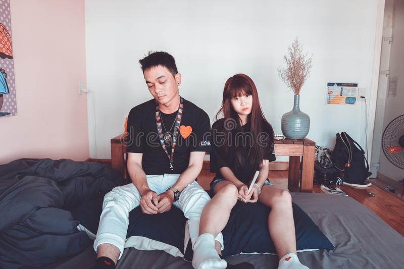 Man and Woman Wearing Black Shirts Sitting on Bed royalty free stock images