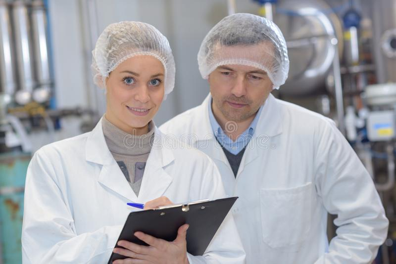 Man and woman wearing hair nets making notes on clipboard royalty free stock photo