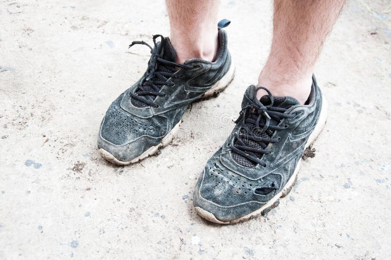 Man or woman in white old and dirty sneakers. Torn sneakers stock photo