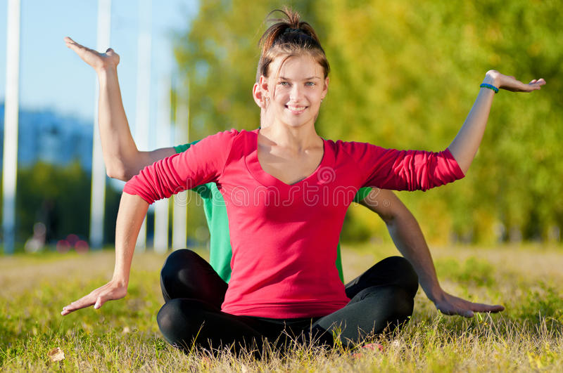 Man and woman woman doing yoga in park stock photo