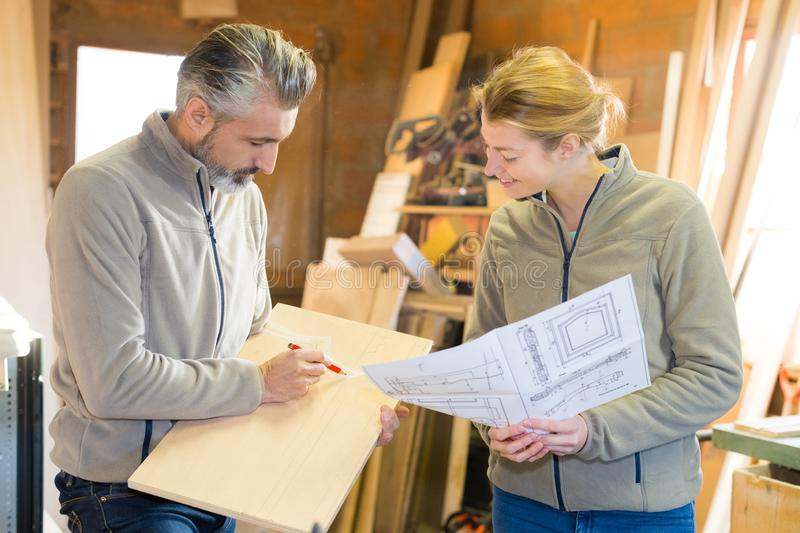 Man and woman work together in furniture design business. Man and women work together in furniture design business man stock photo