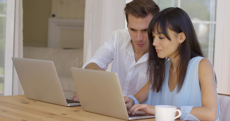 Man and woman working on laptop computers together. Man and women at wooden table working on laptop computers together as they collaborate on a project online stock image