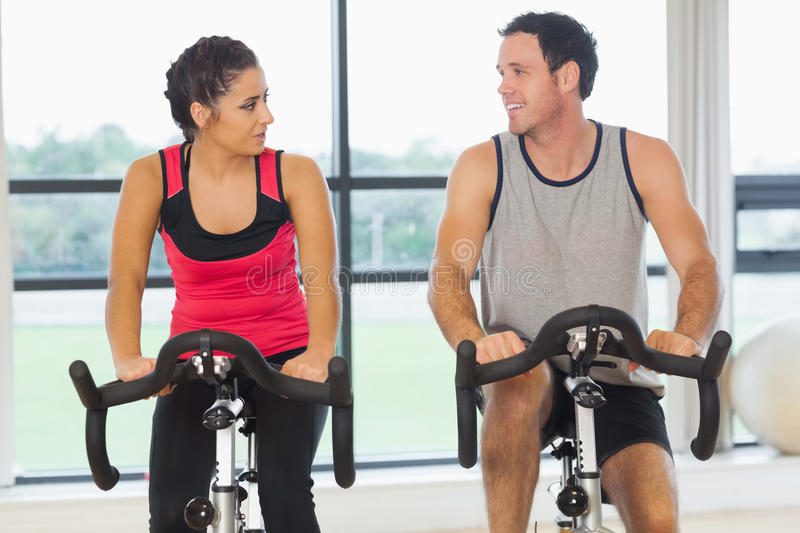 Man and woman working out at spinning class royalty free stock image