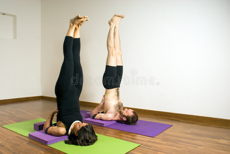 Man and Woman in a Yoga Stretch - Vertical royalty free stock photos