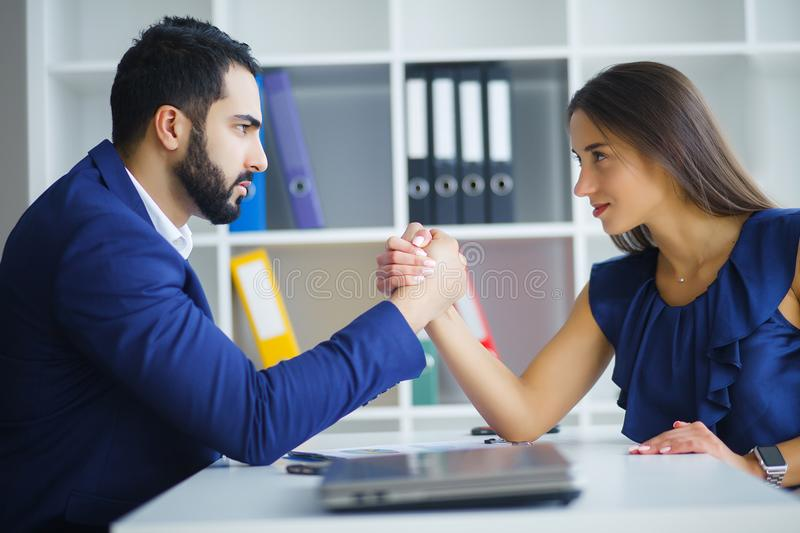 Man and woman arm wrestling on table. Man and women arm wrestling on table stock photos