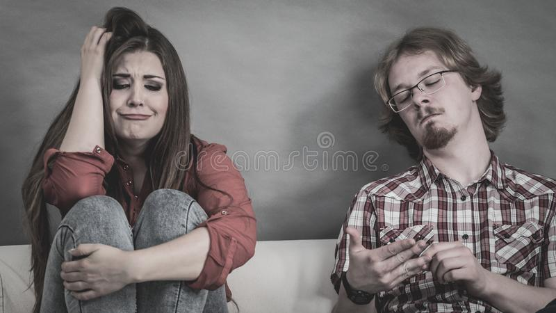 Woman and man after argue on sofa. Man and women being mad at each other after fight. Female crying, boy ignoring. Friendship, couple breakup difficulties and stock photography