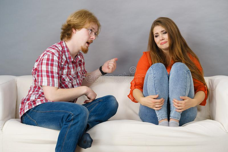 Woman and man after argue on sofa. Man and women being mad at each other after fight. Female is sad. Friendship, couple breakup difficulties and problems concept stock images