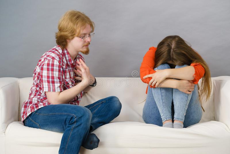 Woman and man after argue on sofa. Man and women being mad at each other after fight. Female is sad. Friendship, couple breakup difficulties and problems concept stock photos