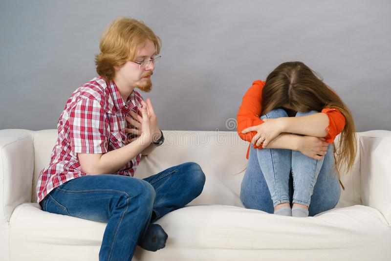 Woman and man after argue on sofa. Man and women being mad at each other after fight. Female is sad. Friendship, couple breakup difficulties and problems concept royalty free stock photo