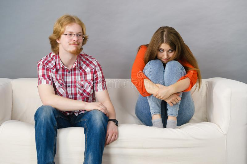Woman and man after argue on sofa. Man and women being mad at each other after fight. Female is sad. Friendship, couple breakup difficulties and problems concept stock photo