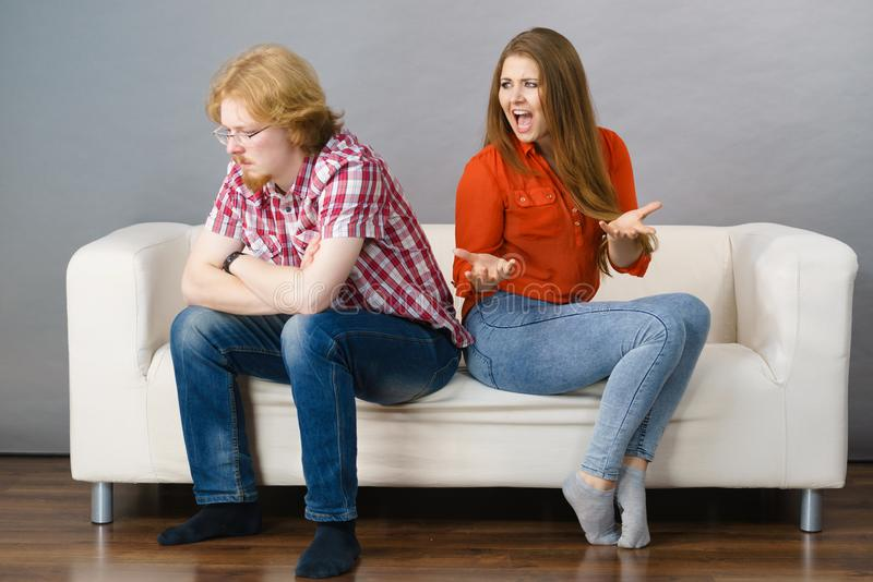 Woman and man after argue on sofa. Man and women being mad, ignoring each other after fight. Friendship, couple breakup difficulties and problems concept stock photo