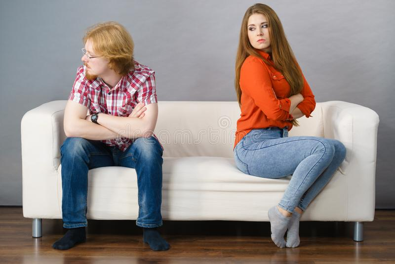 Woman and man after argue on sofa. Man and women being mad, ignoring each other after fight. Friendship, couple breakup difficulties and problems concept stock image