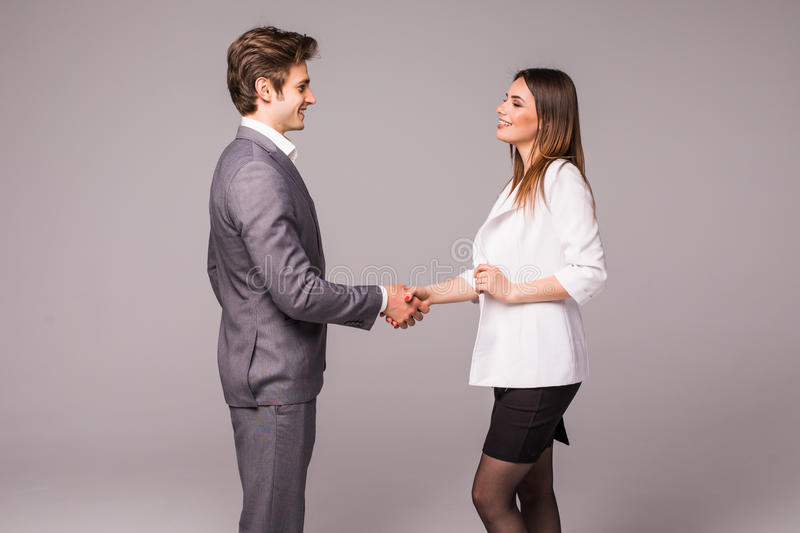 Man and woman business handshake isolated on gray background. Businessman and business woman handshake. stock photo