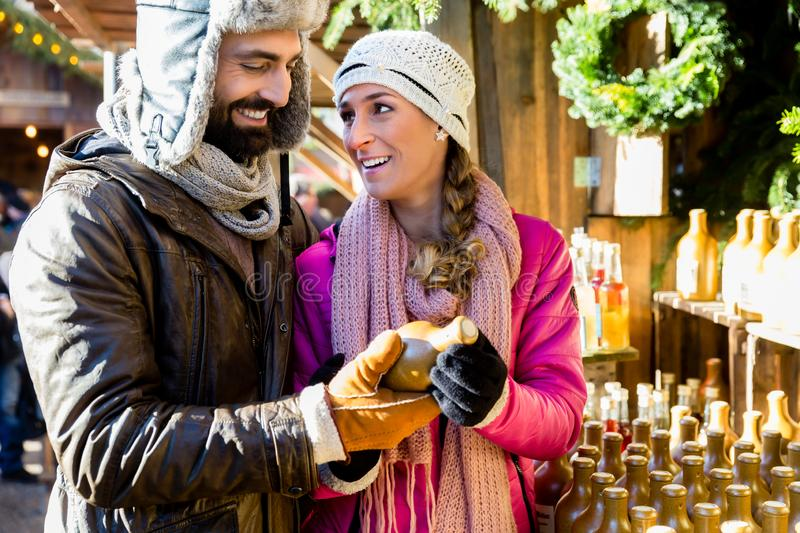 Man and woman buying vases as gift on Christmas market. Man and women buying vases as gift on traditional Christmas market royalty free stock images