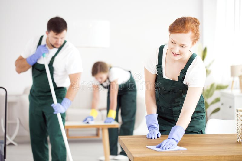 Man and women cleaning house. A men moping the floor and women dusting in gloves and green overalls, cleaning a house royalty free stock photography