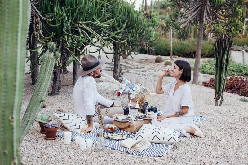 Couple on romantic date lay on picnic blanket. Man and women couple relax in park in beautiful setting with pillows and blankets, on romantic picnic date royalty free stock photography