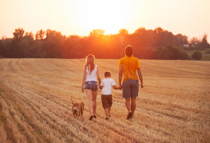 Happy family with dog walking royalty free stock photography