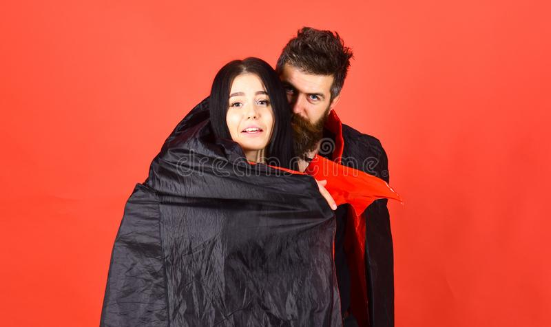 Man and woman dressed like vampire, demon, red background. Couple in love relations, perfect match. Girl on scared face. Man and women dressed like vampire royalty free stock image