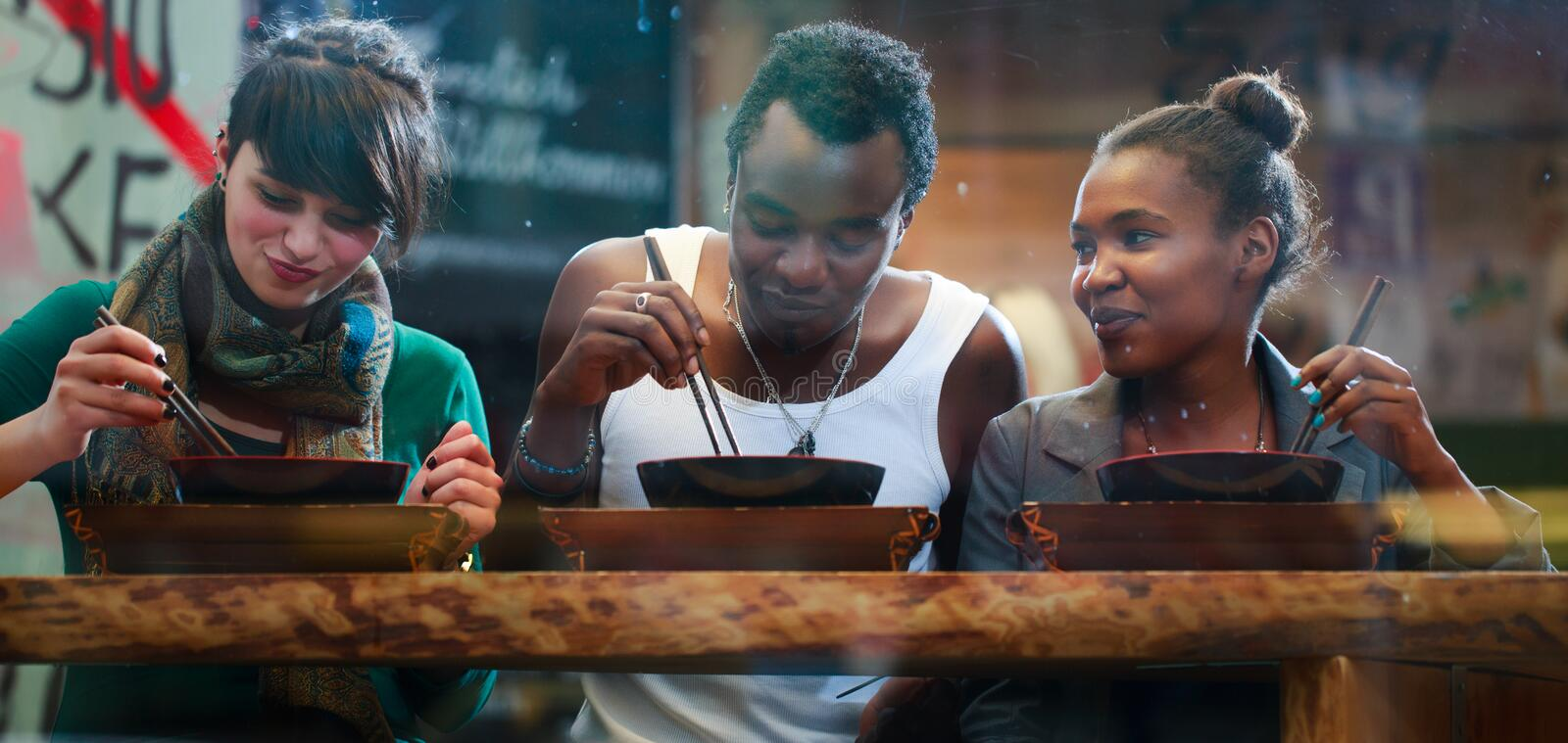 Man and women eating late in Korean eatery. Man and women, black and Latin people, eating late in Korean eatery royalty free stock images
