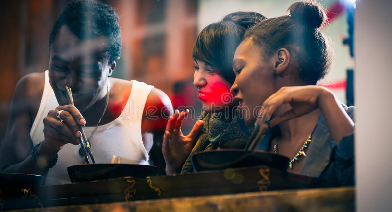 Man and women eating late in Korean eatery. Man and women, black and Latin people, eating late in Korean eatery royalty free stock photos