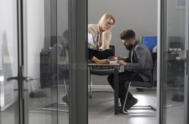 Man and woman entrepreneurs writing business ideas on paper. Business investors discussing business ideas in office royalty free stock image