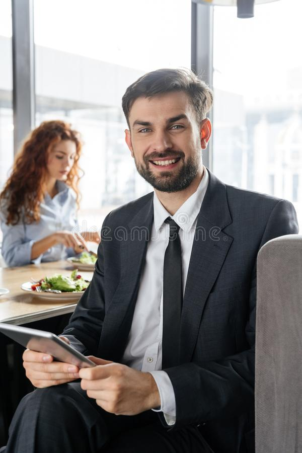 Businesspeople having business lunch at restaurant sitting man close-up holding digital tablet looking camera smiling stock photography