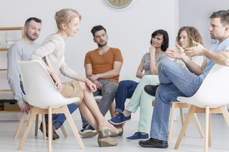 Coaching session in group. Man and women having coaching session about assertiveness in group of people stock images