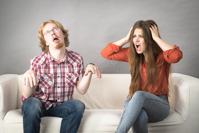 Man and woman having fight. Man and women having horrible fight while sitting on sofa. Friendship, couple breakup difficulties and problems concept stock image