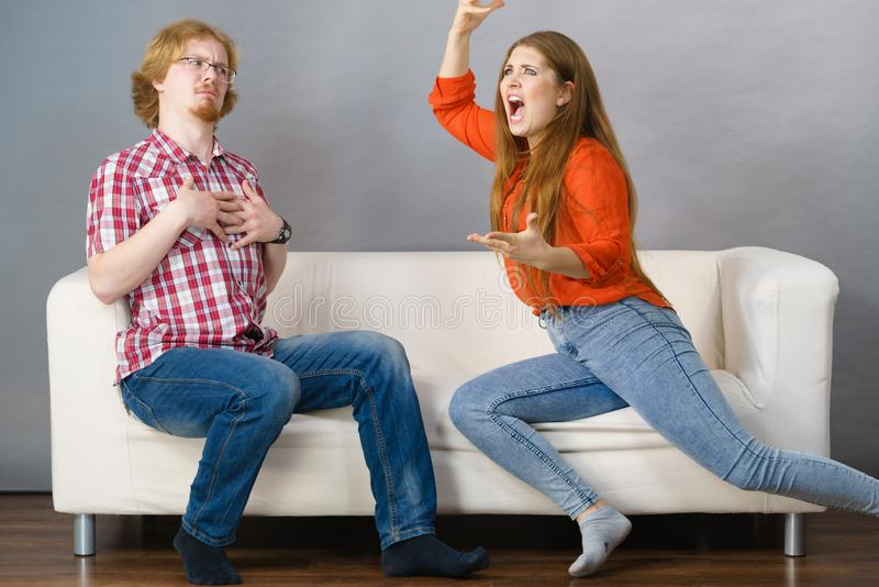 Man and woman having fight. Man and women having horrible fight while sitting on sofa. Friendship, couple breakup difficulties and problems concept stock photos