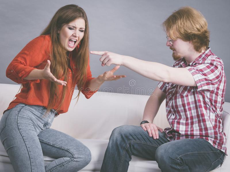 Man and woman having fight. Man and women having horrible fight while sitting on sofa. Friendship, couple breakup difficulties and problems concept stock photography