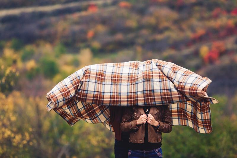 Man and woman hid their heads under brown rug in autumn. Man and women hid their heads under brown rug in autumn royalty free stock photography