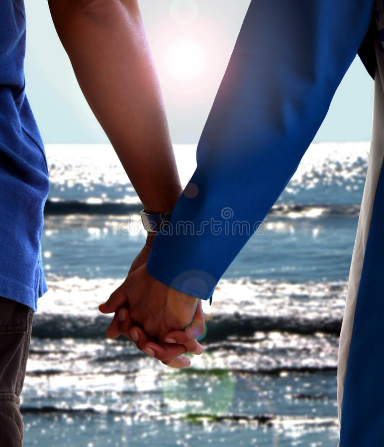 Man and women holding hand during sunrise at the beach. Under bright sunlight royalty free stock image